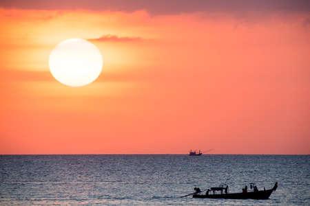 Big sun and a fisherman boat at sunset in Phuket - Thailand Stock Photo