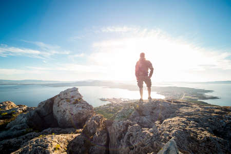 A traveler on the top of the mountain is enjoying the stunning view at sunset in Sardinia, Italy.