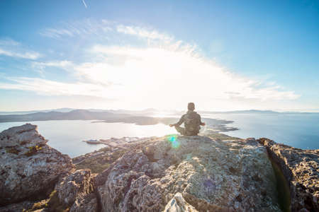A traveler is doing yoga on the top of the mountain at sunset in Sardinia, Italy.