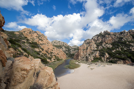 A beautiful natural river between the Italian mountains. River flowing into a beautiful beach in Sardinia. Stock Photo