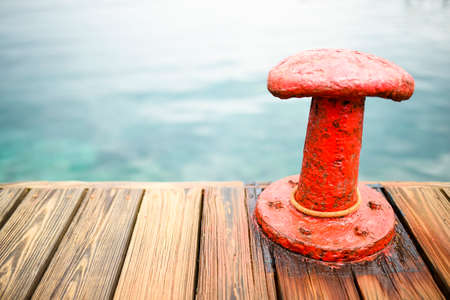 Red bollard with a mooring rope on the pier at the port and sea water in the background.  Sardinia, Italy.