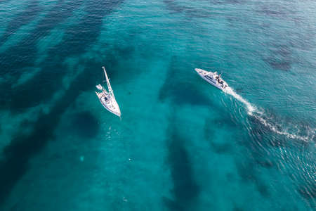 isles: Aerial view of a sail boat and yachts on amazing beach with a turquoise and transparent sea. Emerald Coast, Sardinia, Italy... Stock Photo