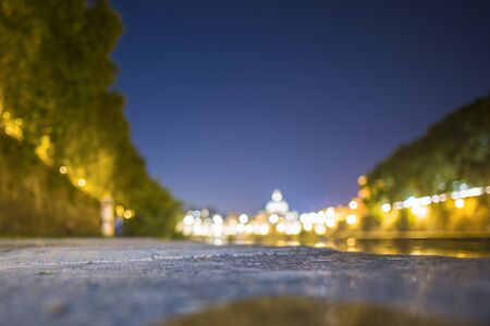 (selective focus, blurred) Blurred nightscape of the Saint Peter Basilica. Photo taken on the banks of the Tiber River with the ground in the foreground