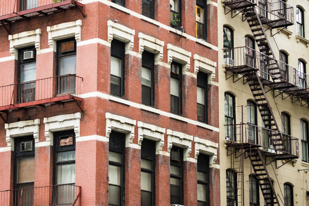 Close-up view of New York City style apartment buildings with emergency stairs along Mott Street in the Chinatown neighborhood of Manhattan NYC. Editorial