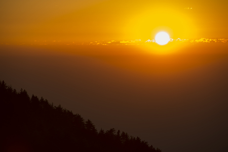 Amazing sunset behind a mountain with the silhouette of trees, Dharamsala, India.