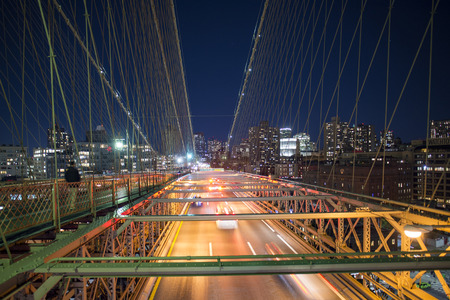 Long exposure picture of cars passing over the illuminated Brooklyn Bridge at night. Manhattan skyline in the background, New York city, USA.
