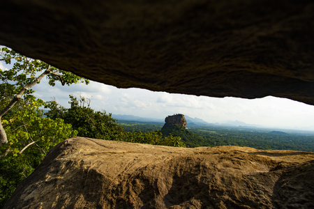 Spectacular view of the Lion rock framed by a rock surrounded by green and rich vegetation. Picture, taken from Pidurangala Rock in Sigiriya, Sri Lanka.
