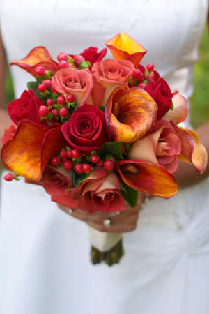 Bride holding bouquet of red and orange roses.