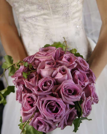 Bride holding bouquet of purple roses.