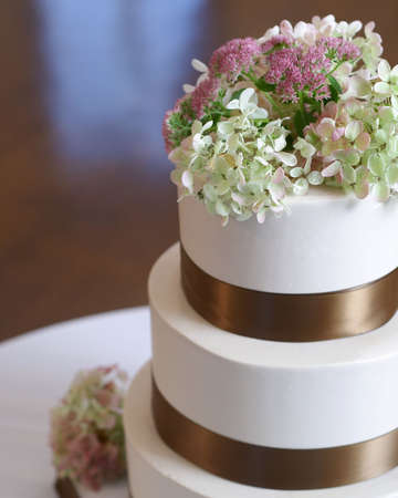 Close-up van witte weding taart met bruin lint en bloemen op de top.