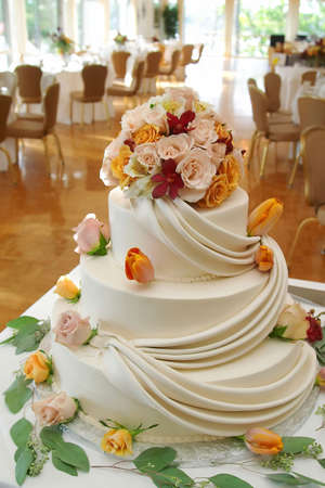 White wedding cake with roses on reception table.