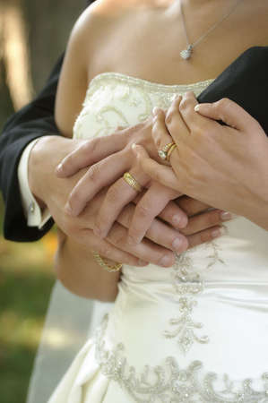 Bride and groom hands showing gold rings over wedding dress photo