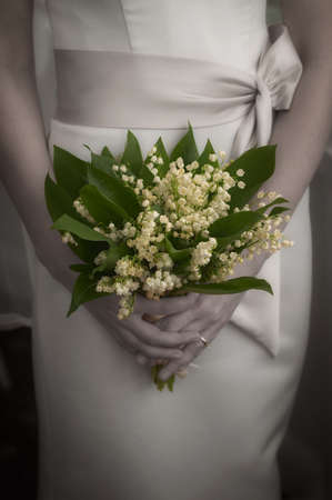 Bride holding bridal wedding bouquet made from lily