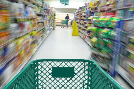 Shopping cart moving through isle of supermarket Stock Photo - 2644961