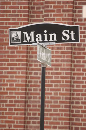 main: Main St street sign infront of brickwall in small town in USA