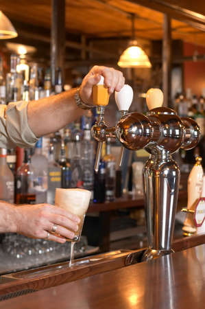 Bartender pouring beer from tap into glass Imagens