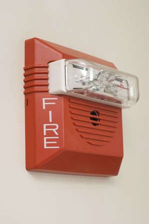 mounted: Red fire alarm mounted on white wall