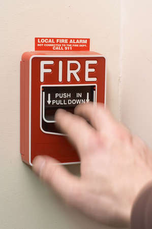 Hand in motion pulling to activate fire alarm Foto de archivo