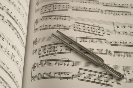 Tuning fork on classic sheet music background photo