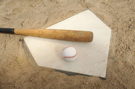 Baseball and bat on home plate of ballpark photo