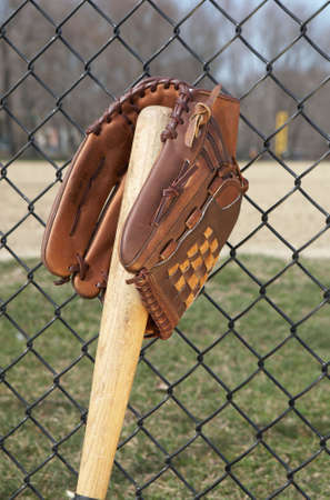 Baseball glove on bat leaniong on fence at ballpark photo