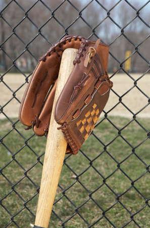 ballpark: Guante de b�isbol en leaniong del palo en la cerca en el ballpark Foto de archivo