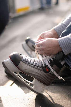 Tying laces of ice hockey skates at skating rink