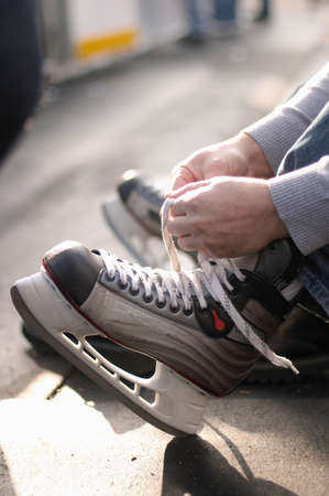 rink: Tying laces of ice hockey skates at skating rink
