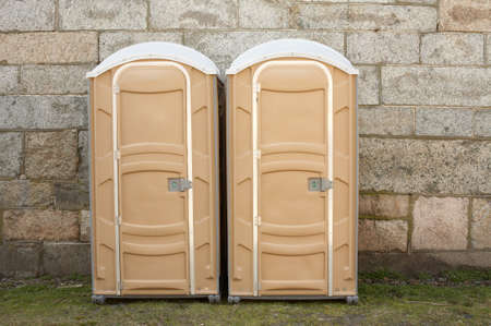 Two portable toilets against stone wall ports potties photo