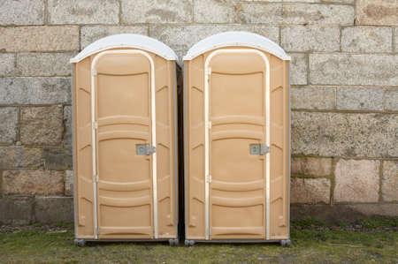latrine: Two portable toilets against stone wall ports potties Stock Photo