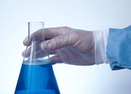 Hand on erlenmeyer flask filled with blue liquid blue tint with copyspace