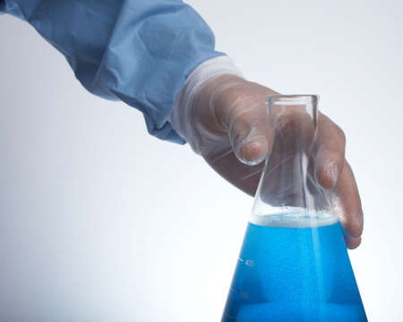 experimenter: Hand holding erlenmeyer flask with blue liquid