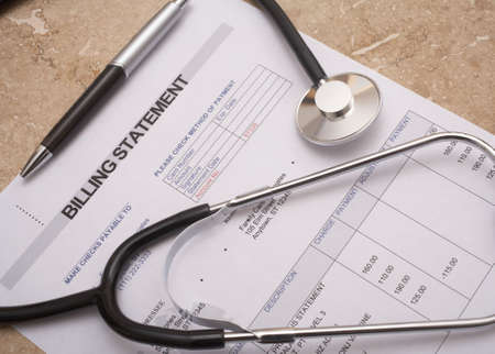 statements: Stethoscope on medical billing statement on table all text is anonymous
