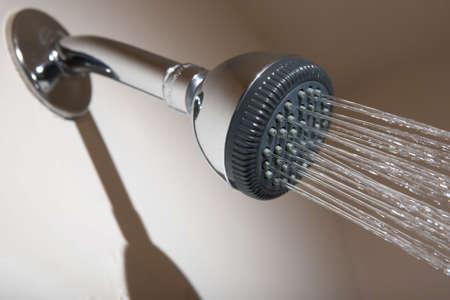 Shower head in bathroom spraying stream of water