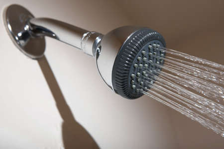 shower stall: Shower head in bathroom spraying stream of water