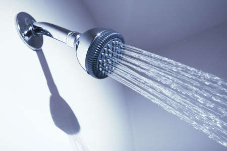 shower stall: Bathroom shower head spraying water on blue background