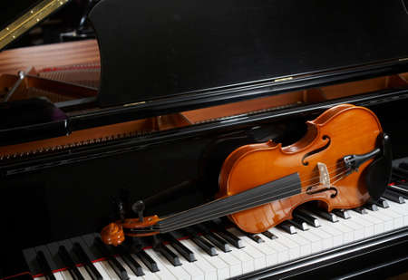 violins: Violin on resting on keys of ebony grand piano Stock Photo