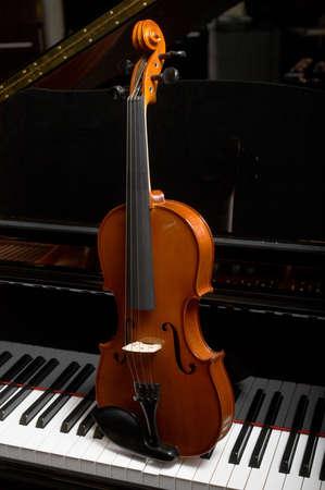 Violin on keys off ebony grand piano Stock Photo