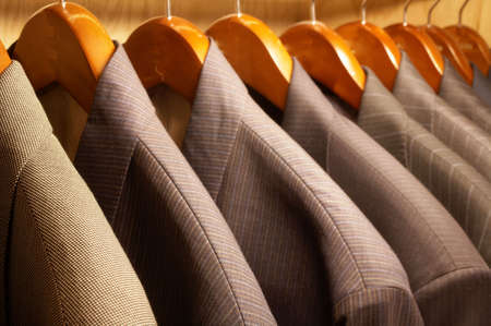 Row of mens suit jackets hanging on hangers photo