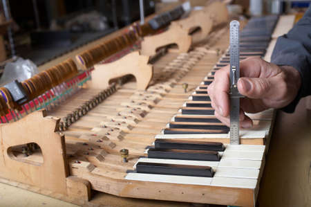 Piano technician at work checking key, DOF focus on hand Standard-Bild