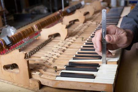 soundboard: Piano technician at work checking key, DOF focus on hand Stock Photo