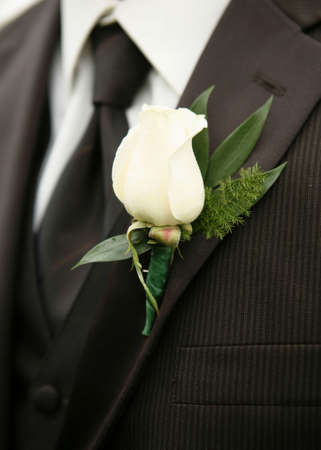 White rose wedding boutonniere on suit of best man