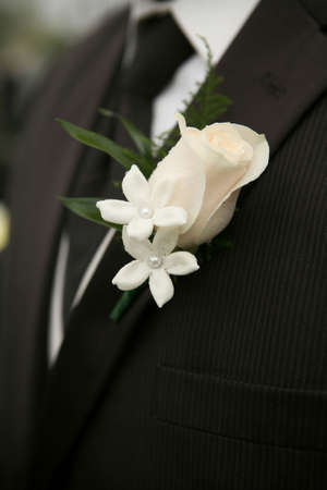 boutonniere: White rose wedding boutonniere on suit of groom