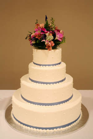 White wedding cake with flowers on reception table