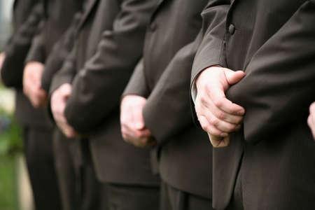 Row of groomsmens hands at wedding reception