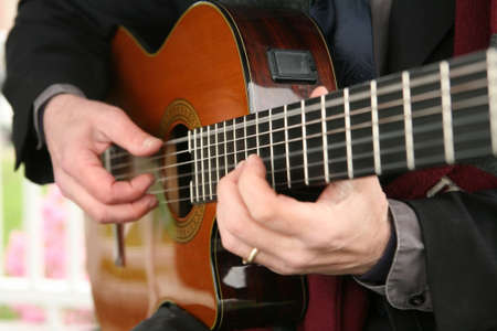 Closeup of mans hands playing classical acoustic guitar DOF focus on neck Stock Photo