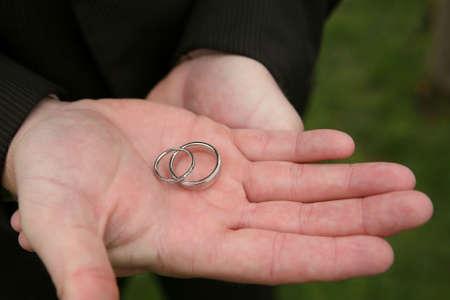 人間の手保有物 2 つの銀の結婚指輪 写真素材