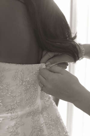 buttoned: Bride getting ready on her wedding day having dress buttoned sepia toned