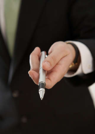 Hand of businessman offering pen to sign contract photo