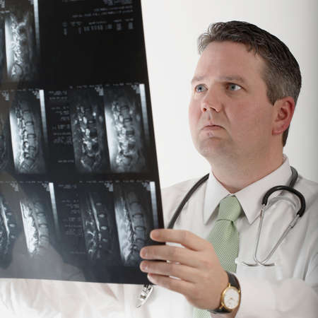Doctor studying mri of human spine and backbone photo